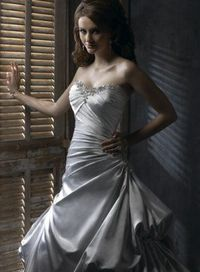 A-line gown with corset closure. Embellished lace motifs highlight the neckline and accent sweeping bustles throughout the front and back train. The asymmetrical bodice magically slims the waist and flows into the L'Amour Satin skirt.