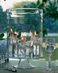 Gather clear apothecary bottles filled with lamp oil and wicks in a hurricane for a stunning DIY centerpiece