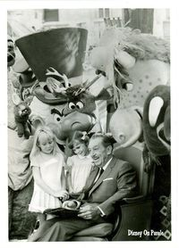 Walt Disney reading a Christmas story to some young Disneyland guests.