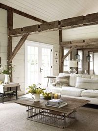 love the beams and the old pigeon cage turned coffee table