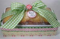 The loaf of bread is sitting in a Kleenex box covered with decorative paper and ribbon.