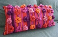 Crochet flower cushion in beautiful pinks/purples and oranges.