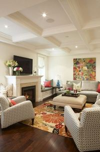I <3 warm tones and splashes of colour in this space! Chic, colourful living room design with ivory cream wall paint colour, coffered ceiling, silver grey velvet sectional sofa, mushroom linen ottoman with nailhead trim, orange black yellow floral rug,...